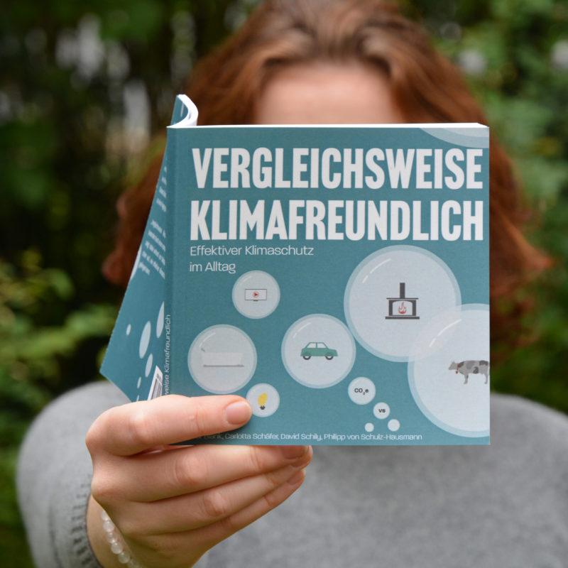 Das Buch Vergleichsweise Klimafreundlich in der Hand von Carlotta